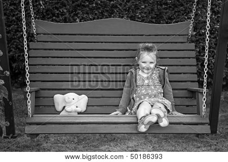 Cute little girl on garden swing wirh sweet smile and cuddly toy poster