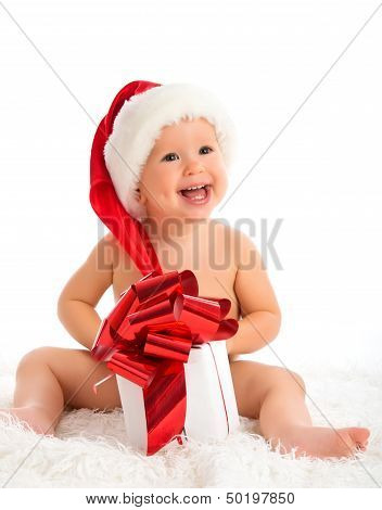 Happy Baby In A Christmas Hat With A Gift Isolated