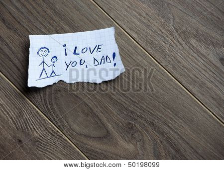 poster of I love you Dad written on piece of paper on a wood background. Space for your text.