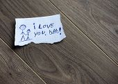 I love you Dad written on piece of paper on a wood background. Space for your text. poster