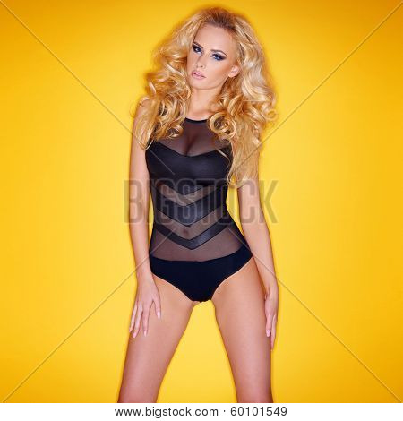Sultry glamorous slender young blond woman in a sexy leotard standing against an yellow studio background