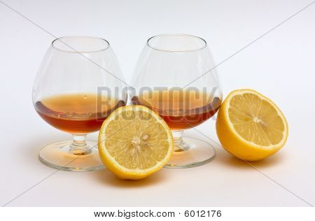 Two Glasses Of Cognac And Two Halves Of A Lemon