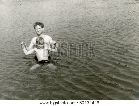 KURSK, USSR - CIRCA 1960s: An antique photo shows portrait of father and son swimming in the river
