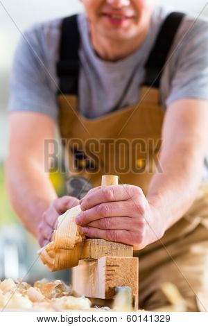 Carpenter working with a wood planer on workpiece in his workshop or carpentry