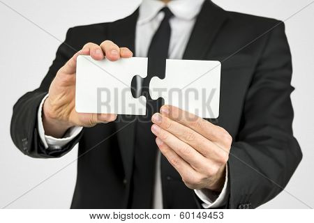Businessman Holding Two Puzzle Pieces