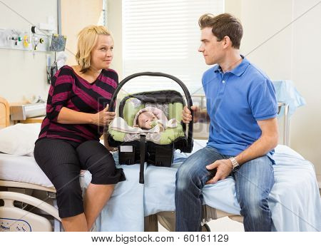 Mid adult couple with baby carrier looking at each other while sitting on hospital bed poster