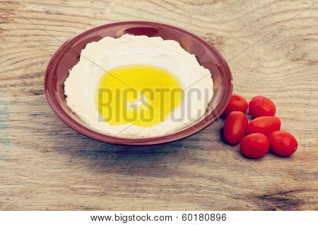 Lebanese food of Labneh Yogurt cheese and cherry tomato on wooden background with retro filter effec