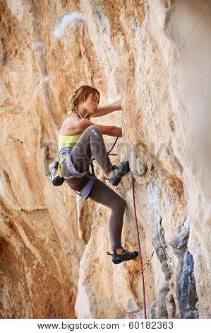 Young female rock climber a face of a cliff