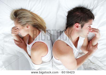 Coppia sdraiata a letto dopo aver avuto una lotta. Matrimonio Trouble