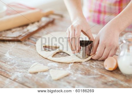 cooking and home concept - close up of female hands making cookies from fresh dough at home