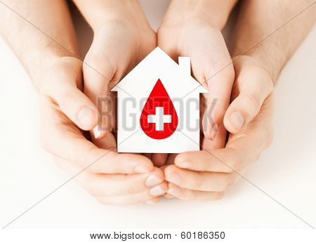 healthcare, medicine and blood donation concept - male and female hands holding hands holding white paper house with red donor sign
