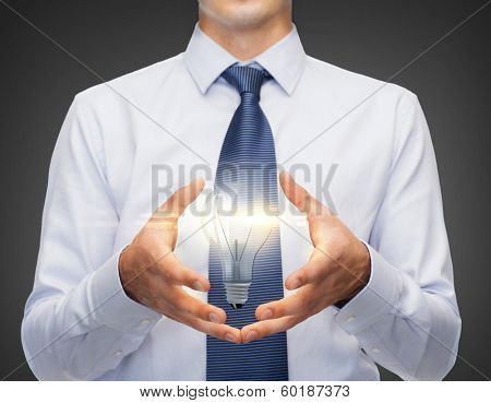 business and office, advertising, people concept - friendly young buisnessman holding something in his hand