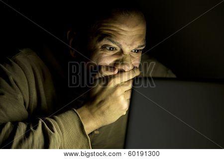 Man shocked at something on his laptop at night