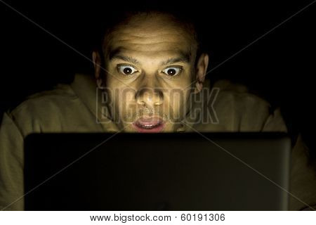 Man with a shocked face on his laptop at night