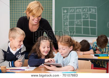 Three Happy Young Students Using A Tablet In Class