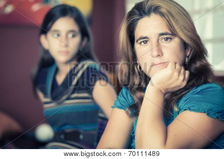 Teenager problems - Sad and worried mother with her rebellious teenage daughter on the background