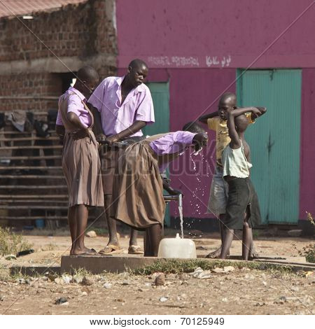 TORIT, SOUTH SUDAN-FEBRUARY 20 2013: Unidentified students drink from a well in the town of Torit, South Sudan