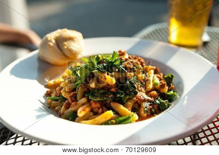 Broccoli rabe dish with sausage over penne pasta presented in a white dish. poster