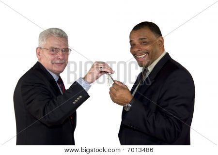 caucasian senior manager handing over a key to his partner