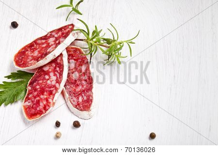 Salami on wooden board with rosemary poster