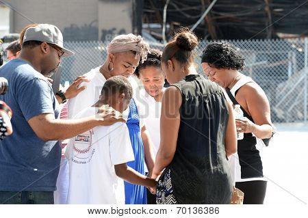 FERGUSON, MO/USA -  AUGUST 15, 2014: Group prays at the site of destroyed Quick Trip after Police Chief Thomas Jackson release of the name of the officer that shot Michael Brown.