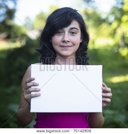 Teengirl holding clean white sheet paper, outdoors (banner for your message)