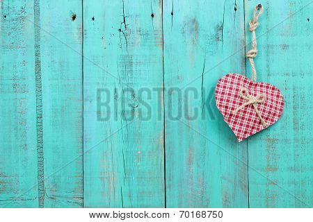 Red checkered heart hanging on distressed antique teal blue fence