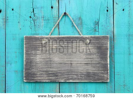 Blank rustic sign hanging on antique teal blue distressed fence