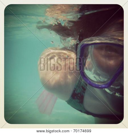 fun instagram image of young girl underwater snorkelling