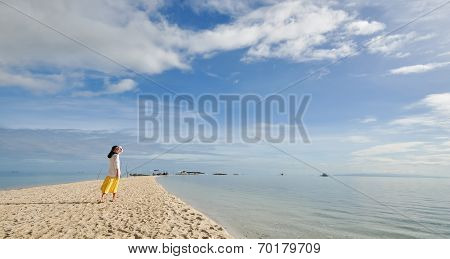 young girl walks on long narrow beach