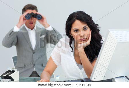 Brunette Businesswoman Annoyed By A Man Looking Through Binoculars