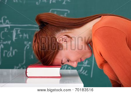 Student Leaning Head On Book In Classroom