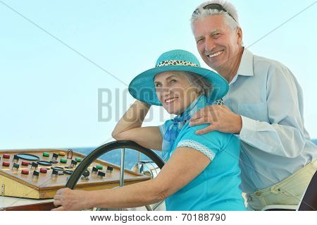 Retired couple ride in boat on sea