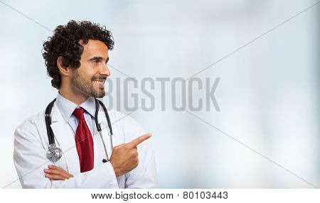 Portrait of a smiling doctor pointing his finger