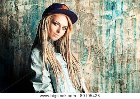 Modern teenage girl with blonde dreadlocks. Jeans style. Modern generation.