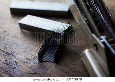 Reloading. Reloading a stapler, on a old wooden desk.