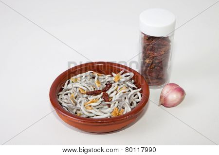 Earthenware bowl with imitation young eels cooked with garlic oil and pepper poster