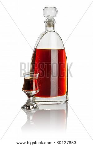 Carafe and schnapps glass filled with brown liquid