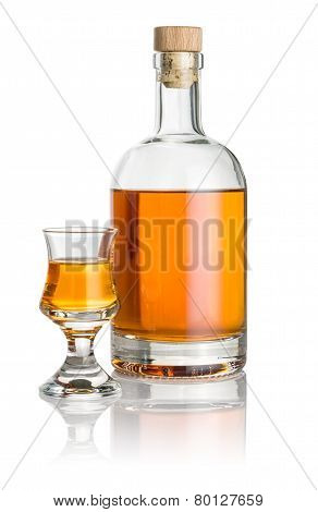 Bottle and schnapps glass filled with amber liquid