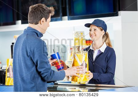 Smiling female seller giving popcorn paperbag and drink to man at concession stand in cinema