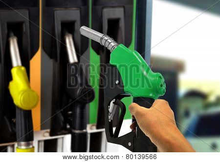 Hand Holding Gas Nozzle At Gas Station
