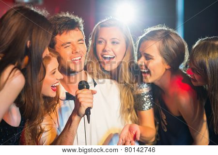 Happy friends singing karaoke together in a bar