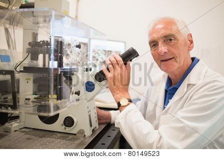Biochemist using large microscope and computer at the university