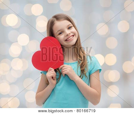 love, charity, holidays, children and people concept - smiling little girl with red heart over lights background