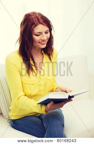 leasure and home concept - smiling teenage girl reading book and sitting on couch at home