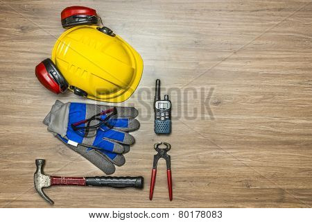 Background of personal safety accessories on a wooden surface. Items include a hard hat with ear protection attached, safety goggles, working gloves, a hammer, pincers and a cb radio
