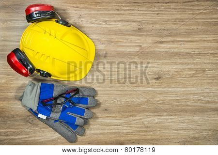 Background of personal safety accessories on a wooden surface. Items include a hard hat with ear protection attached, safety goggles and working gloves