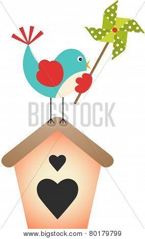 Bird with pinwheel on top of the birdhouse