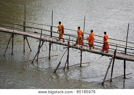 Buddhist Monks Crossing Bamboo Bridge In Luang Prabang, Laos