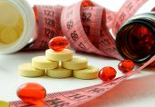 Measuring tape and bottle with pills. supplements of weight loss poster